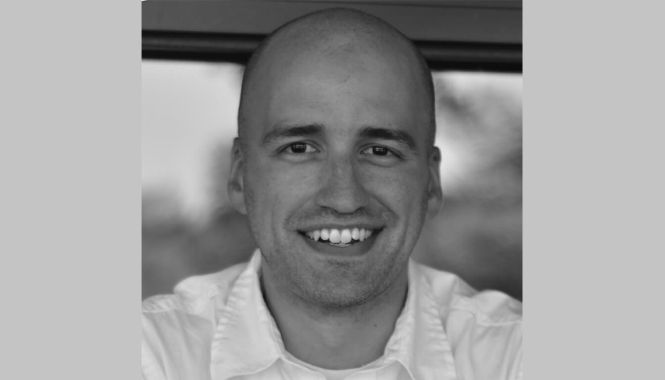 Profile photo of Adrian Roselli in black and white. He's smiling looking directly at the camera, wearing a white shirt.