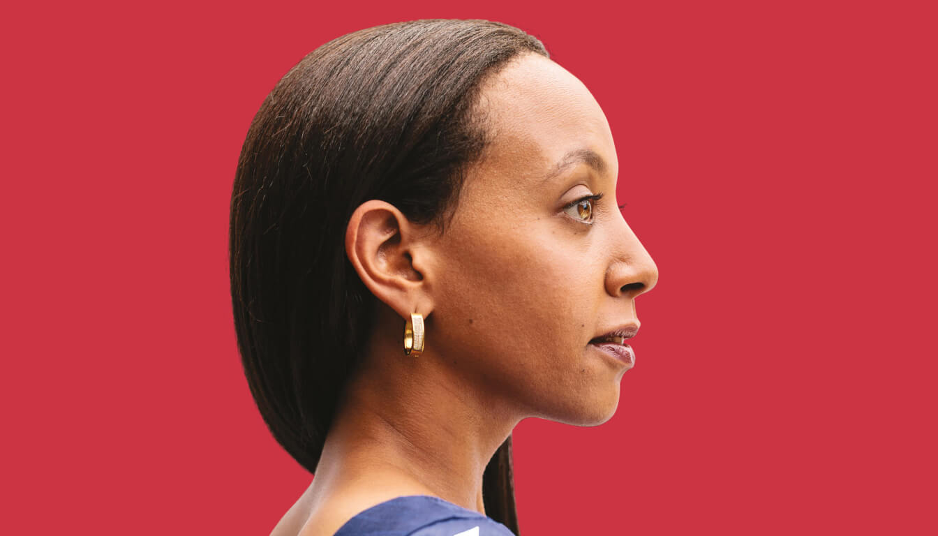 Profile photo of Haben Girma from the side, in front of a bright red background. She's wearing a navy blouse and gold earrings.