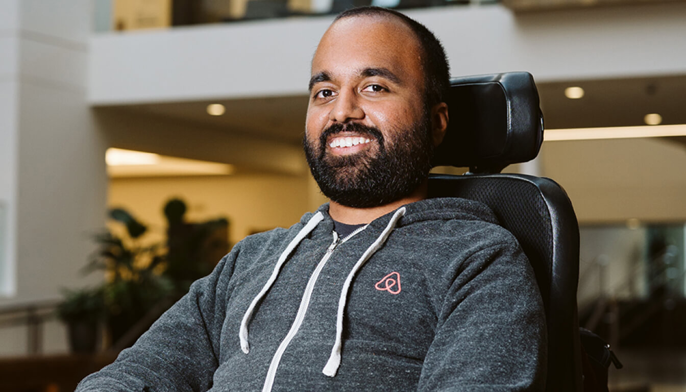 Srin Madipalli smiling to the camera from his electric wheelchair. His wearing a dark grey zip-up hoodie with the Airbnb logo on his chest.