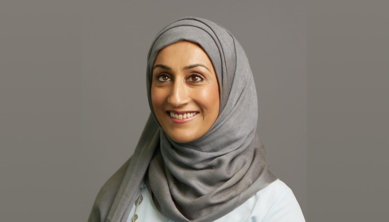 Sumaira Latif smiling to the camera. She's wearing a grey hijab and a light blue blouse.