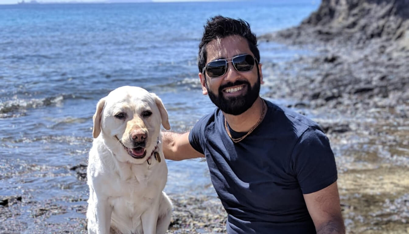 Amit Patel smiling to the camera on a beach with his right arm around his yellow lab guide dog, Kika. Amit is wearing a navy t-shirt and sunglasses.