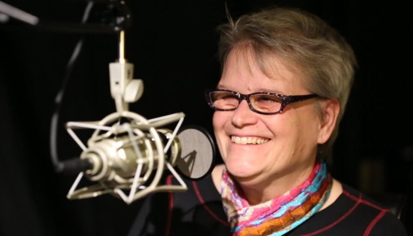 Cathy Kudlick smiling and looking off to the side while talking into a podcast microphone. She's wearing a black blouse with red stitching, a colorful scarf and glasses.