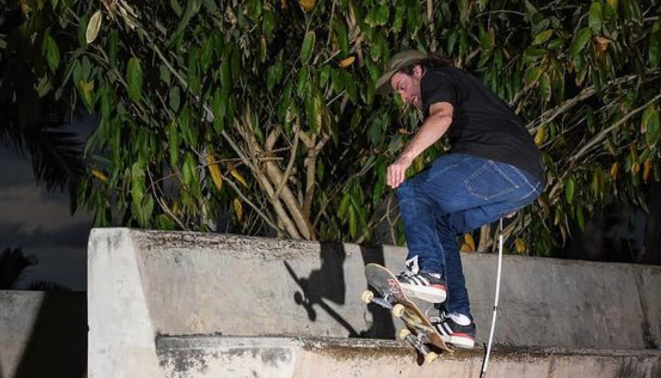 Dan Mancina doing a skateboard trick with his white cane in his right hand. He's wearing blue jeans, black t-shirt, Adidas sneakers and a cap.