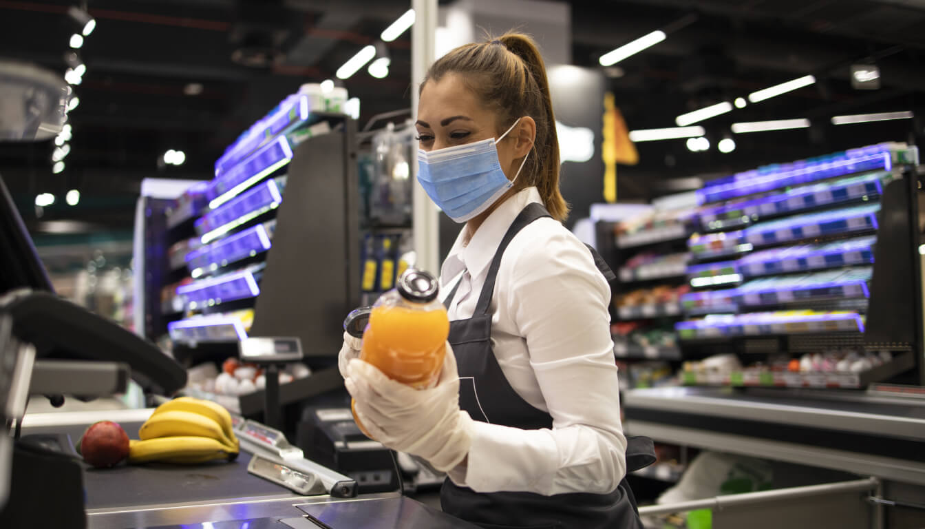 Female supermarket cashier scanning groceries while wearing a face mask and gloves.