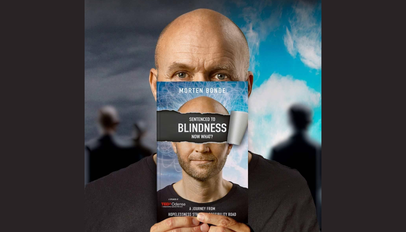 """Morten Bonde holding up his book """"Sentenced to Blindness Now What?"""" in front of his face, so only his eyes are visible. On the book cover, the title is blocking his eyes."""