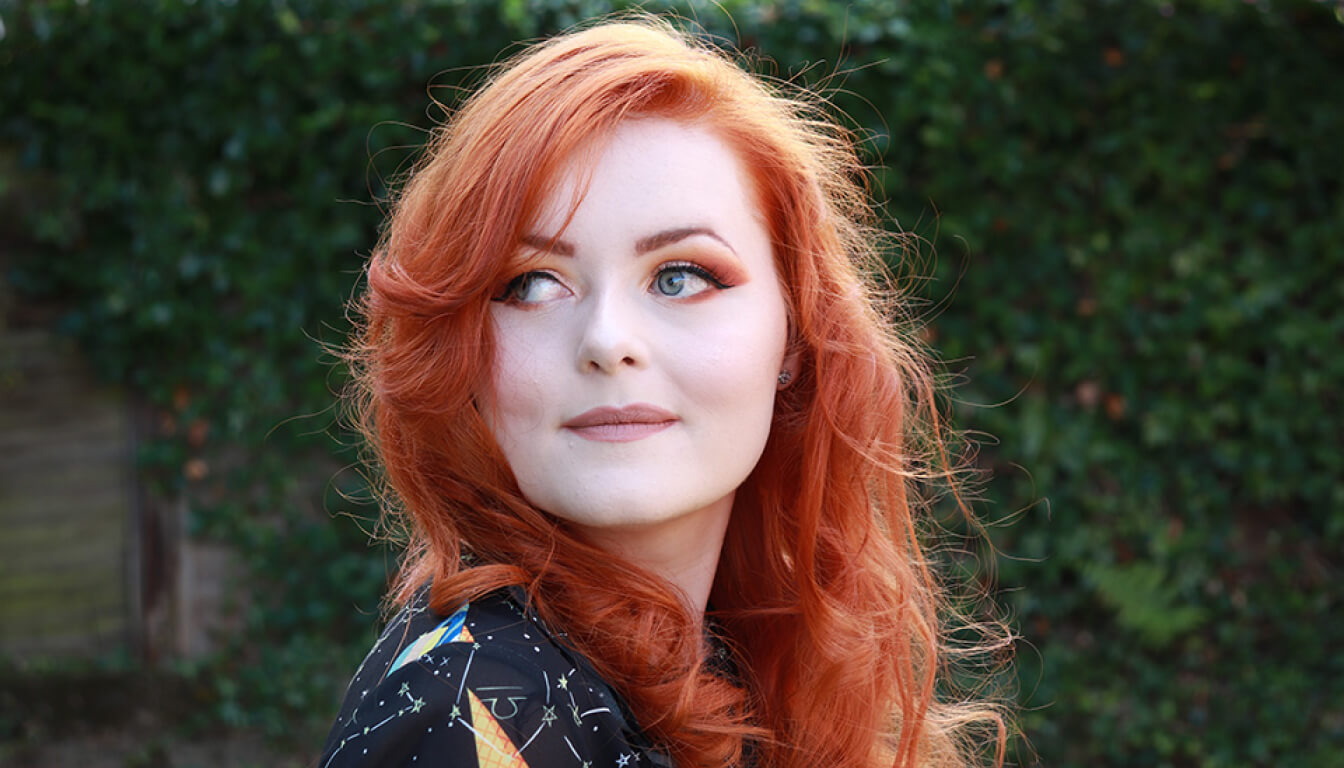 Lucy Edwards looking off to the side. She's wearing a black blouse with a night sky constellation pattern and colorful eye makeup that matches her red hair.