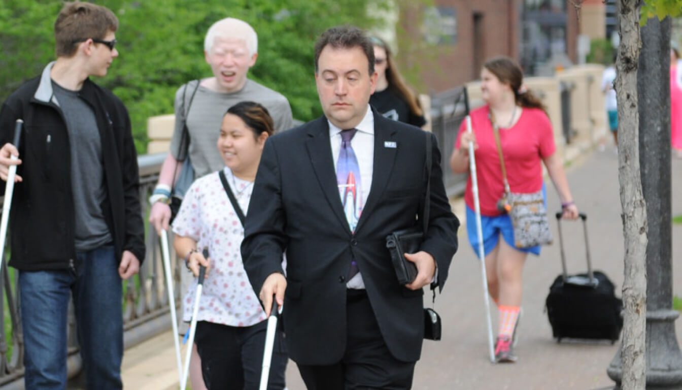 Mark Riccobono walking on the street with his white cane. He's wearing a black suit, white shirt and a colorful tie.