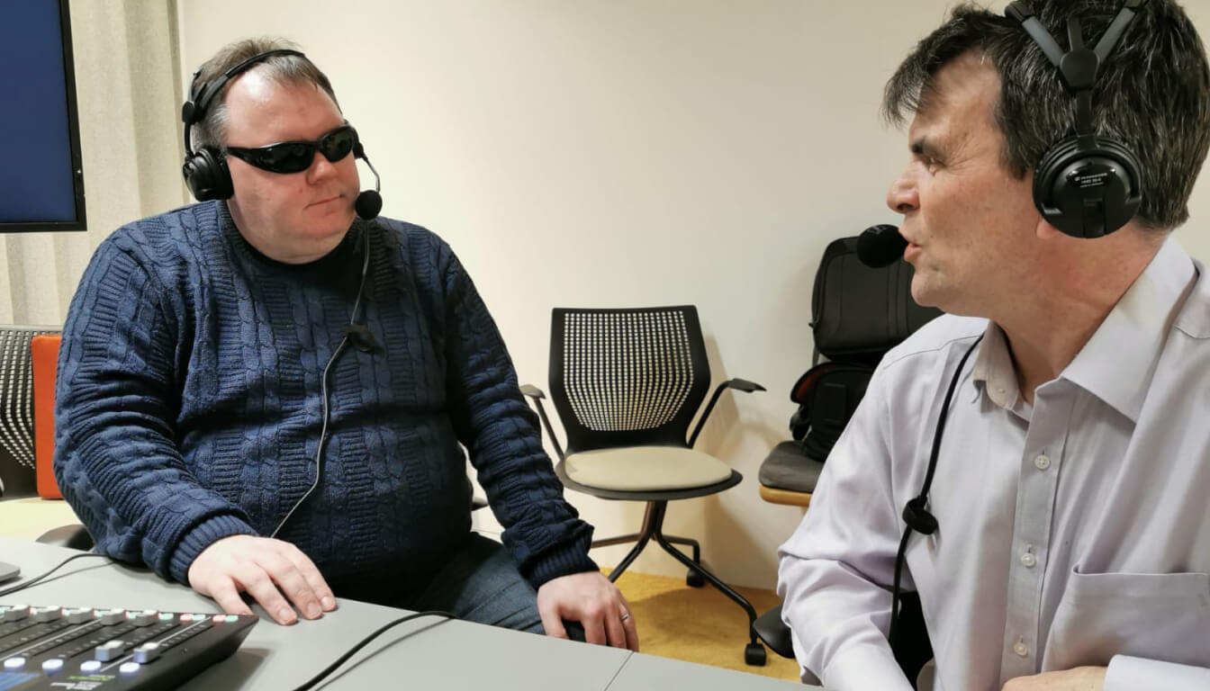 Robin Christopherson and Steven Scott talking to each other wearing podcasting headphones. Steven, on the left, is wearing a navy cable-knit sweater and black sunglasses. Robin is wearing an off-white shirt.